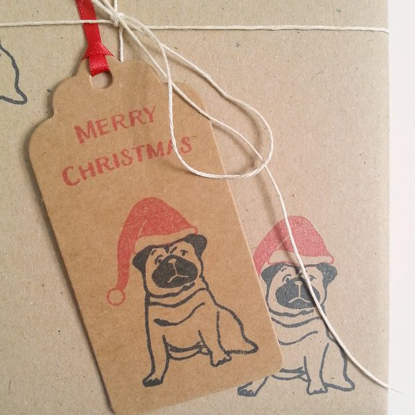 Close up of gift wrapped present, with Christmas Gift Tag, with Pug design.