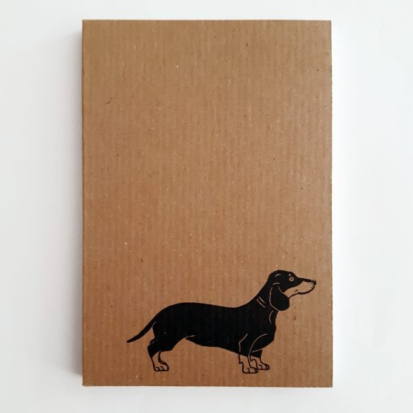 sausage dog notebook. brown ribbed kraft notebook, featuring sausage dog in bottom right corner of cover.