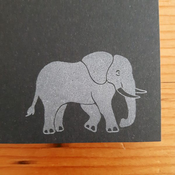 Close up of charcoal grey elephant notebook, showing hand printed white elephant in bottom right corner of front outer cover