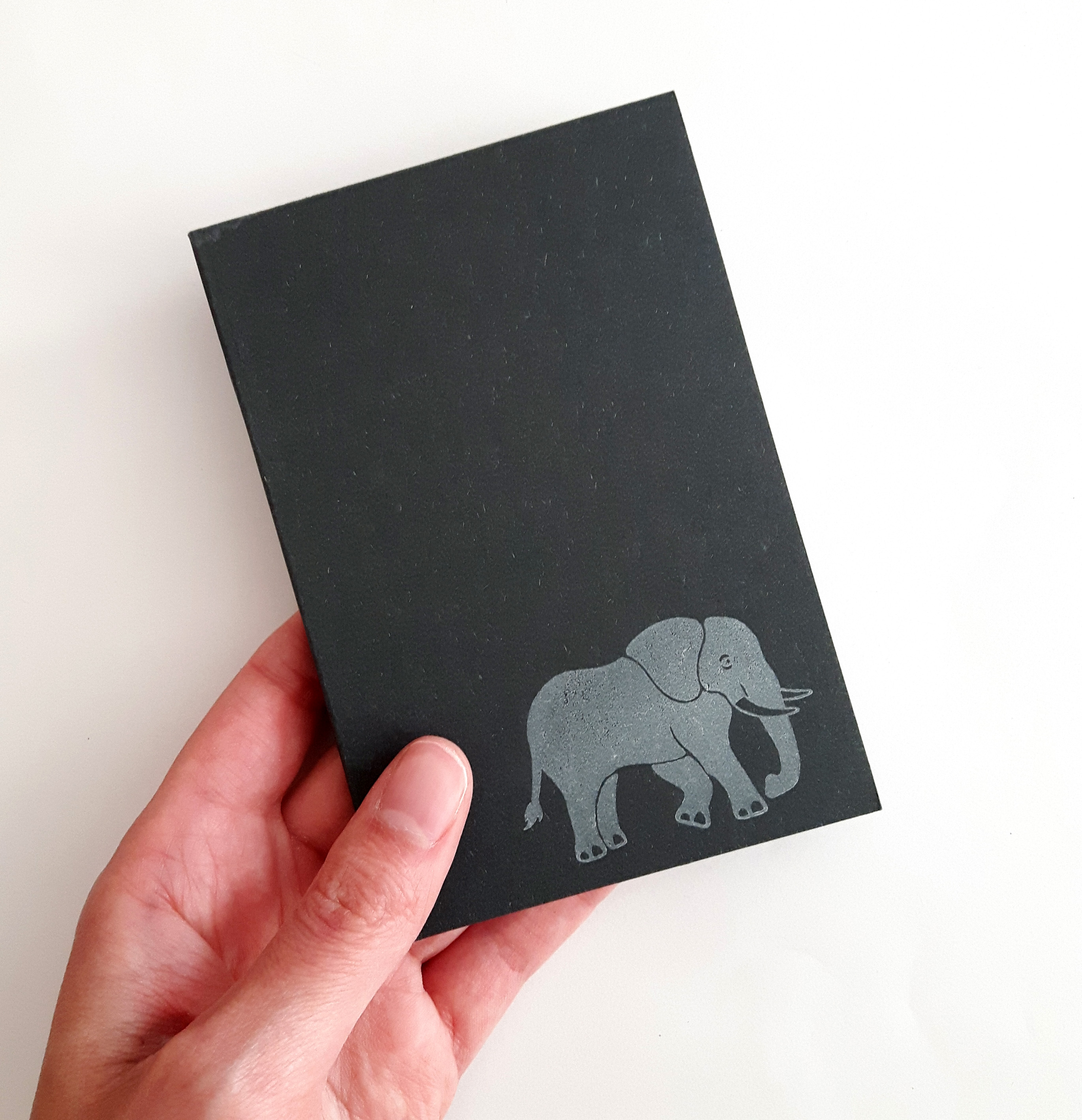 elephant notebook, held in a hand to show size. Charcoal grey notebook, with white elephant in bottom right corner