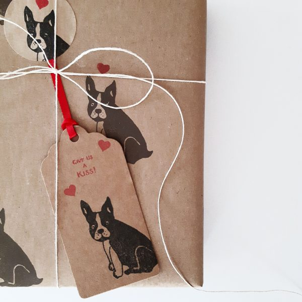 close up of gift wrapped present with french bulldog gift tag with love hearts