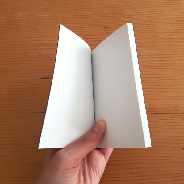 notebook held open to show plain white unlined pages inside
