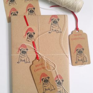 Christmas presents, wrapped in Christmas Pug wrapping paper, including gift tags and twine.