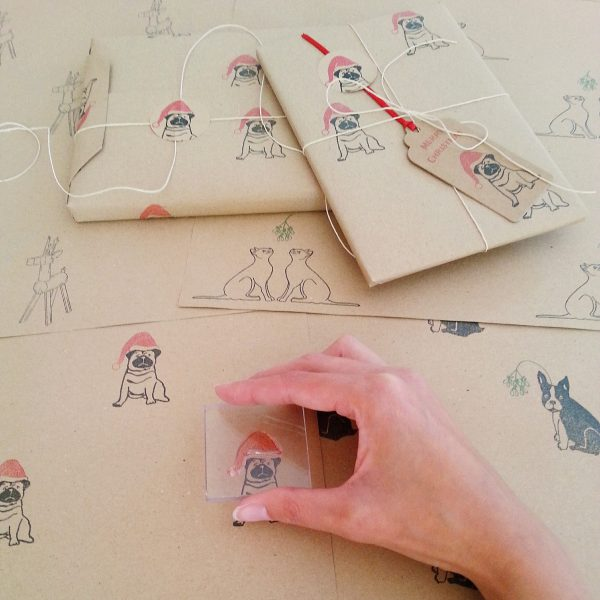 An image showing the hand printing process behind my Christmas Pug wrapping paper. Me adding a santa hat to my Pedro the Pug design
