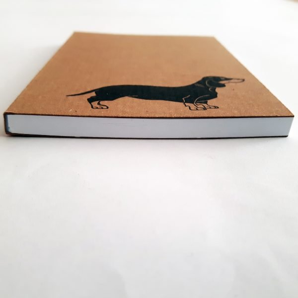 angled image of sausage dog notebook, to show white sheets inside the pad, and perfect binding to the left edge of the pad.