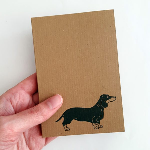 sausage dog notebook, hled in the hand, to show size - passport-sized
