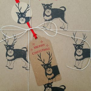Close up of Christmas present gift wrapped in reindeer dog wrapping paper, with matching gift tag