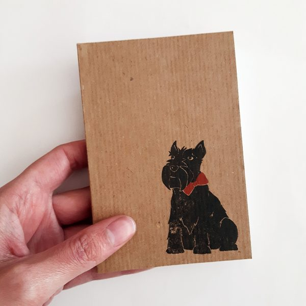 Scottie dog kraft notepad, being held to show size