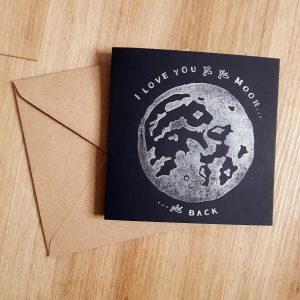 Flat lay black card with Kraft envelope. Moon print with I Love You to the Moon and Back message