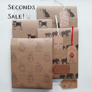 Seconds sale image with folded wrapping paper sheets and gift tags, designs include Santa, schnauzer, elephant, cat and Christmas Frenchie
