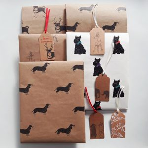 assortment of folded seconds gift wrap sheets and gift tags. Designs include dachshund, scottie dog, schnauzer, reindeer, bunnies, elephants and songbirds