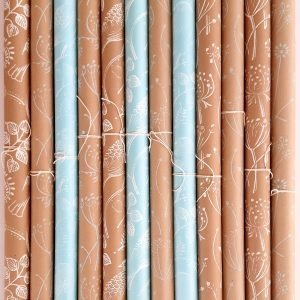 Many wrapping paper rolls, all handmade, printed onto blue and brown kraft