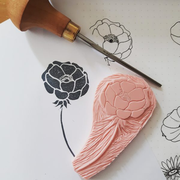 Block carving of a peony, next to original floral sketches