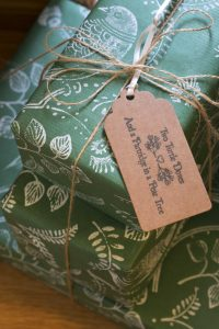 Christmas gift wrapped in forest green Christmas wrapping paper, with turtle dove print.