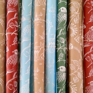 assortment of hand printed Christmas wrapping paper rolls, in blue, brown, green, and red kraft.