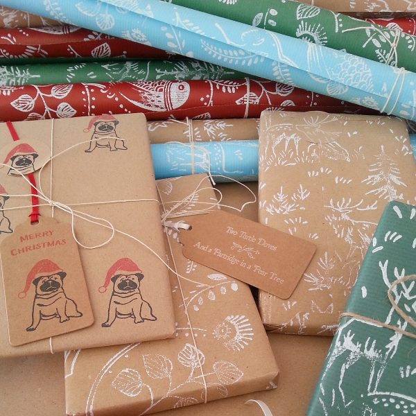 assortment of Christmas gift wrapping, including Christmas Pug wrapping paper and gift tag