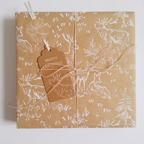 Christmas present wrapped in recycled christmas wrapping paper. with deer print