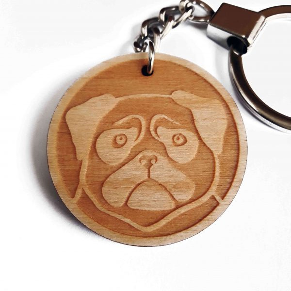 close up of pug keyring, wooden laser cut keyring, with silver tone key chain and split ring