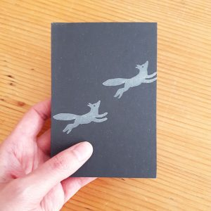 fox notebook, being held to show size - passport-sized, charcoal grey notebook with white prancing foxes