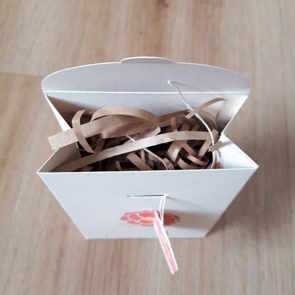 Showing shredded kraft paper inside floral gift box