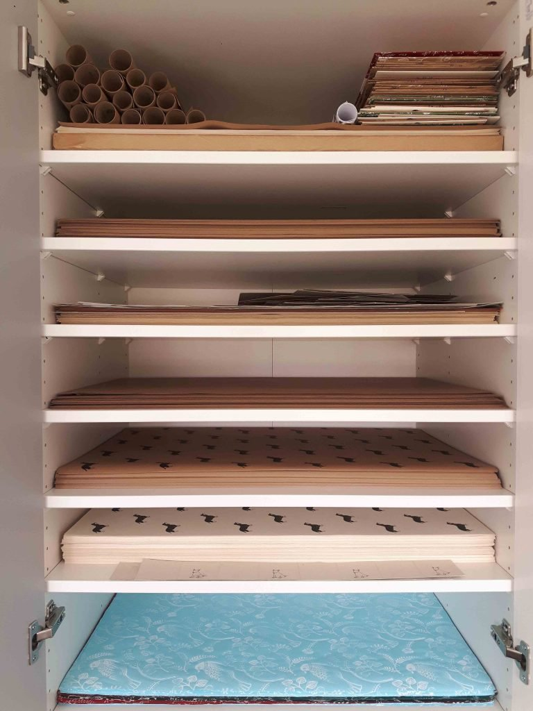 wardrobe with neatly stacked wrapping paper sheets