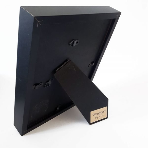 reverse of frame - all black, with a brown kraft branding sticker, which red Wrapped By Alice. Frame has an arm on the back for standing, as well as hooks for hanging on the wall.