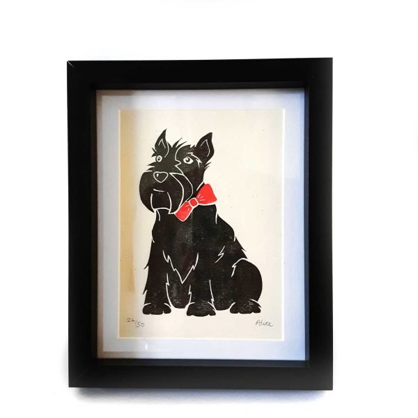 Framed Scottie Dog art print. Bold print of a stylised scottish terrier, wearing a red bow tie. Printed on cream card, with a white mount, in a black box frame.