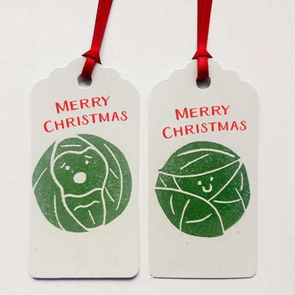 2 brussel sprouts gift tags. cream tags with green sprouts and red merry christmas message, and red satin ribbon
