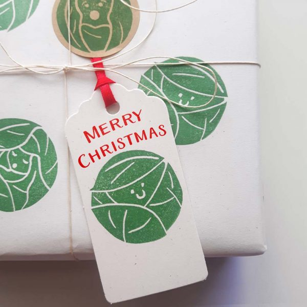 present wrapped in brussel sprouts wrapping paper with a matching gift tag