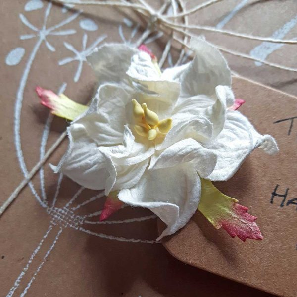 close up of white gardenia on paper flower gift tag