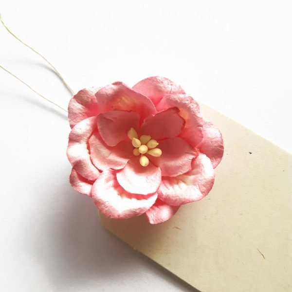 close up of pink paper rose on cream gift tag