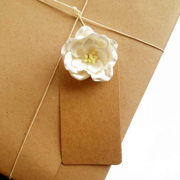 kraft tag with white rose, attached to gift wrapped present