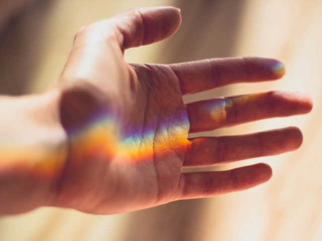 Rainbow reflected in the palm of a hand.