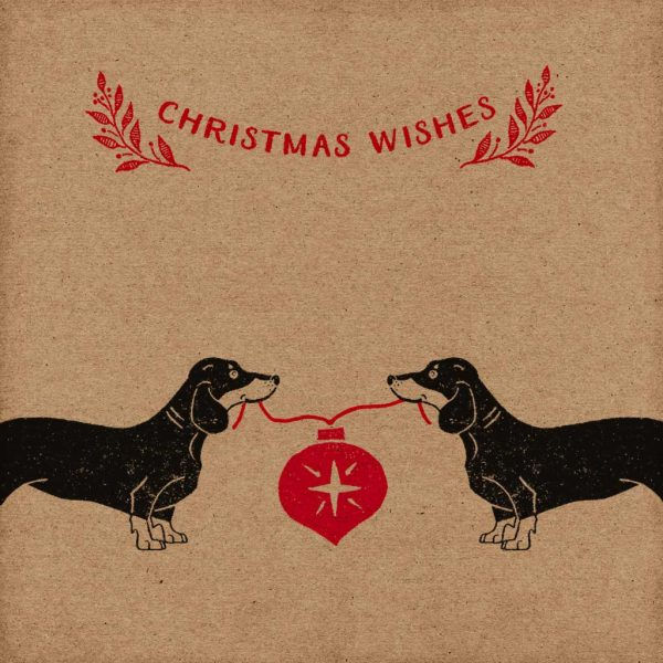 dachshund christmas card. kraft card with hand printed dachshunds holding red bauble and 'Christmas Wishes' message above.