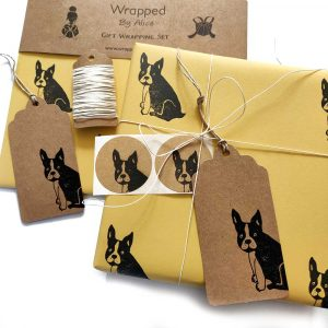 image showing contents of yellow frenchie gift wrap set - present wrapped ion yellow paper, with brown kraft tag, and other items from the set scattered around - gift tag, stickers, hemp cord and spare paper.