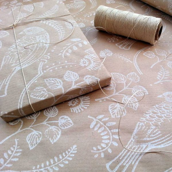 gift wrapped in turtle dove wrapping paper, sat on matching recycled wrapping paper roll..
