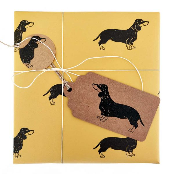 present wrapped in sausage dog print yellow wrapping paper, tied with natural hemp cord, and with matching kraft gift tag and sticker