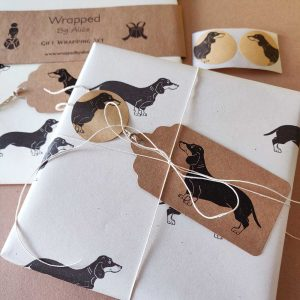 Contents of a dachshund gift wrapping set from Wrapped By Alice. Cream paper and kraft tags and stickers, plus hemp cord.