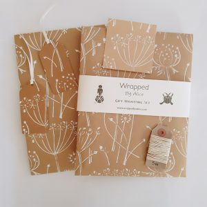 Floral gift wrap set set. 2 folded wrapping paper sheets, 2 gift tags, 4 stickers, 5m hemp cord. With white seed heads pattern on brown kraft.