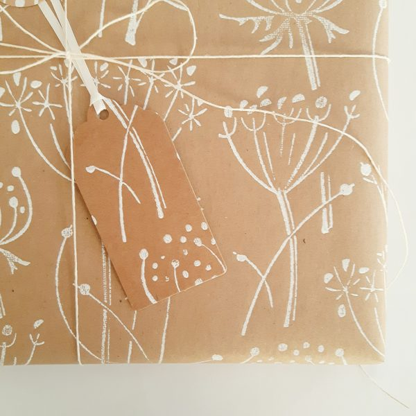 Close up of present wrapped in floral gift wrap - brown kraft wrapping paper and gift tag, both with pattern of white seed heads.