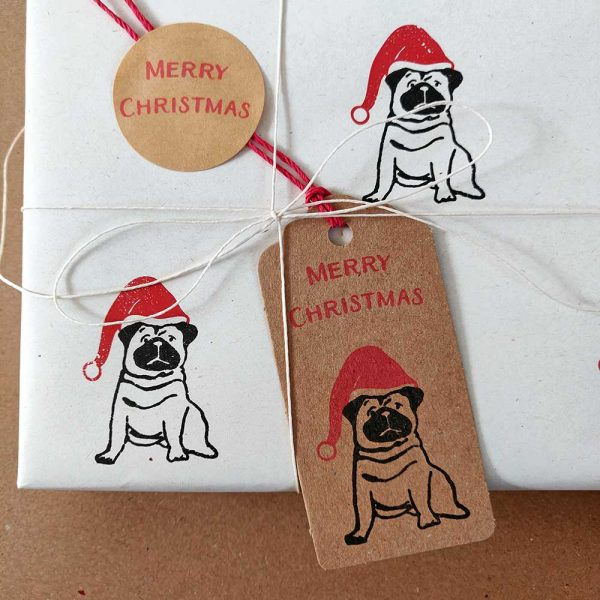 Close up of Christmas Pug gift tag attached to present wrapped in cream, christmas pug wrapping paper