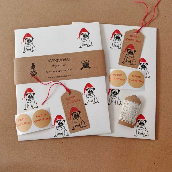 Christmas Pug gift wrap set. Cream wrapping paper, and brown kraft accessories, featuring a black pug wearing a santa hat.